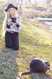 Nettes kleines Mädchen steht nahe See mit Kamera still Stockfotografie