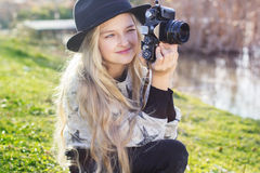 Nettes kleines Mädchen steht nahe See mit Kamera still Lizenzfreie Stockbilder