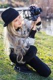 Nettes kleines Mädchen steht nahe See mit Kamera still Stockfoto