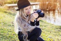 Nettes kleines Mädchen steht nahe See mit Kamera still Lizenzfreies Stockfoto