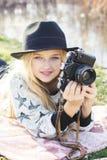 Nettes kleines Mädchen steht nahe See mit Kamera still Stockbild