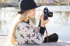 Nettes kleines Mädchen steht nahe See mit Kamera still Stockbilder