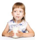 Nettes kleines Mädchen trinkt Milch unter Verwendung des Trinkhalms Stockfotos