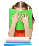 Nettes kleines Mädchen versteckt sich hinter einem Buch Stockfotografie