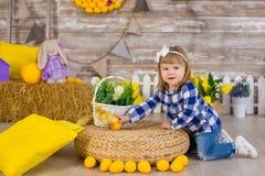 Nettes kleines Mädchen, welches die rustikalen Jeans spielen Verstecken mit einem Huhn sitzt an einem Heuschober trägt Das Konzep lizenzfreie stockbilder