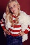 Nettes kleines Mädchen whith langes blondes Haar im Pelzmantel, der im Studio lächelt und aufwirft Lizenzfreies Stockfoto