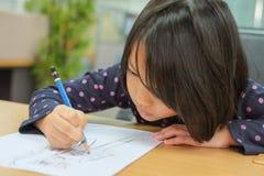 Nettes kleines Mädchen zeichnet Karikatur stockfoto