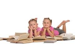 Nettes kleines Mädchen zwei, das auf Stapel der Bücher liegt lizenzfreies stockfoto