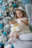 Nettes kleines Mädchen in bklom Kleid, das in einem Stuhl sitzt und öffnet Kasten mit Geschenk für Hintergrund Weihnachtsbaumblau Lizenzfreies Stockbild