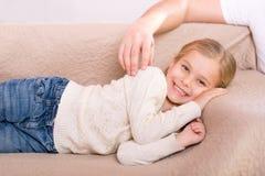 Nettes kleines Mädchen, das auf dem Sofa liegt Stockfoto