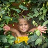 Nettes kleines Mädchen, das aus dem Grün heraus späht Stockfoto