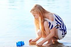 Nettes kleines Mädchen, das draußen Origamiboot hält Lizenzfreies Stockfoto