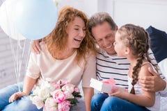 Nettes kleines Mädchen, das ein Geschenk von ihren Großeltern empfängt Lizenzfreie Stockbilder