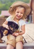 Nettes kleines Mädchen, das Hundewelpen umarmt Stockbild