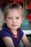 Nettes kleines Mädchen, das rote Korne trägt. Lizenzfreies Stockbild