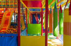 Nettes kleines Mädchen haben Spaß am weichen Spielplatz im Freien Lizenzfreies Stockfoto