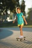 Nettes kleines Mädchen mit Skateboard draußen Stockfoto