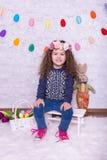 Nettes kleines süßes Mädchen in einer Ostern-Dekoration zu Hause lizenzfreie stockbilder