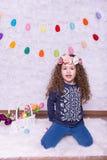 Nettes kleines süßes Mädchen in einer Ostern-Dekoration zu Hause lizenzfreie stockfotos