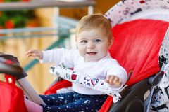 Nettes kleines schönes Baby, das in der Pram- oder Spaziergänger- und Warten Mutter sitzt Glückliches lächelndes Kind mit blauen  Stockbild