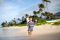Nettes Kleinkind, das auf einen tropischen Strand läuft Stockfoto