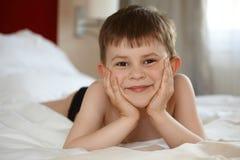 Nettes Kleinkind, das im Bett lächelt Stockfotografie