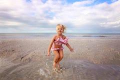 Nettes Kleinkind, das im Wasser auf dem Strand durch den Ozean spritzt und spielt stockfoto