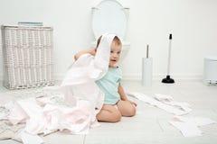Nettes Kleinkind, das mit Toilettenpapier spielt lizenzfreies stockbild