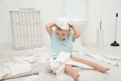 Nettes Kleinkind, das mit Toilettenpapier spielt lizenzfreies stockfoto