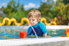 Nettes Kleinkind, das mit Wasser durch den Swimmingpool im Freien spielt Lizenzfreie Stockfotos
