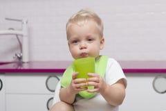 Nettes Kleinkind in einem grünen Schellfisch mit einem Plastikglastrinkwasser in der modernen Küche Stockfotos