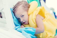 Nettes Kleinkind in einer aufblasbaren Weste, die auf einem Sonnenruhesessel liegt Stockfoto