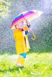 Nettes Kleinkind mit dem Regenschirm, der im Regen spielt Stockbild