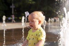 Nettes Kleinkind mit lustigem Gesichtsgefühle playiong mit gefrorenem Flusswasser im Brunnen Lizenzfreie Stockbilder