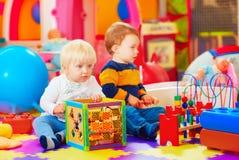 Nettes Kleinkind scherzt in der pädagogischen Mitte, Kindergarten lizenzfreie stockfotografie