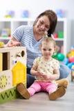 Nettes Kleinkindbaby, das mit busyboard spielt Mutter- oder Babysitterunterrichtskind in der Kindertagesstätte Kind-` s p?dagogis lizenzfreies stockbild