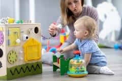 Nettes Kleinkindbaby, das mit busyboard spielt Mutter- oder Babysitterunterrichtskind in der Kindertagesst?tte Kind-` s p?dagogis lizenzfreie stockfotografie