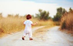 Nettes Kleinkindbaby, das weg entlang den Weg am Sommerfeld läuft Lizenzfreie Stockfotografie