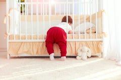Nettes Kleinkindbaby, das zu Hause in das Feldbett im Kindertagesstättenraum klettert Lizenzfreie Stockfotos