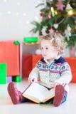 Nettes Kleinkindmädchen, das ein Buch unter einem Weihnachtsbaum liest Stockbild