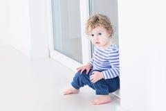 Nettes Kleinkindmädchen, das am großen Fenster im Wohnzimmer sitzt Lizenzfreie Stockbilder