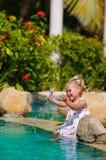 Nettes Kleinkindmädchen, das im Swimmingpool spritzt Lizenzfreie Stockfotos