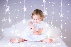 Nettes Kleinkindmädchen, das mit ihrem Spielzeugbären zwischen weichen Lichtern in der Sternform spielt Stockbilder