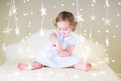 Nettes Kleinkindmädchen, das mit ihrem Spielzeugbären zwischen weichen Lichtern in der Sternform spielt Lizenzfreies Stockfoto