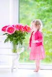 Nettes Kleinkindmädchen, das mit Pfingstrosenblumen spielt Stockbilder