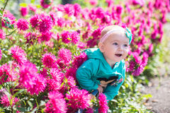 Nettes Kleinkindmädchen in den rosa Blumen im Frühjahr Stockfotografie