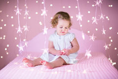 Nettes Kleinkindmädchen in einem weißen Bett zwischen rosa Lichtern Stockfotos