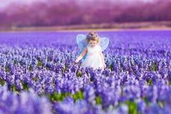 Nettes Kleinkindmädchen im feenhaften Kostüm auf einem Blumengebiet Lizenzfreies Stockfoto