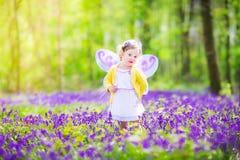 Nettes Kleinkindmädchen im feenhaften Kostüm im Glockenblumewald Stockfotos