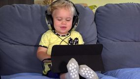 Nettes Kleinkindmädchen mit Kopfhörern unter Verwendung der Tablette und Hören Musik stock video